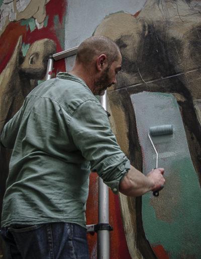 Philippe Hérard applique le rouleau sur un mur de la rue des Couronnes par J Barret