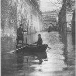 Deux sauveteurs en barque rue Fresnel, lors de la crue de janvier 1910. Crédit Parimagine.