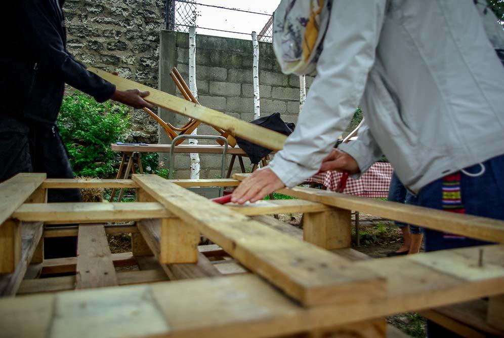Bénévoles des Brigades vertes défaisant des palettes pour construire des jardinières