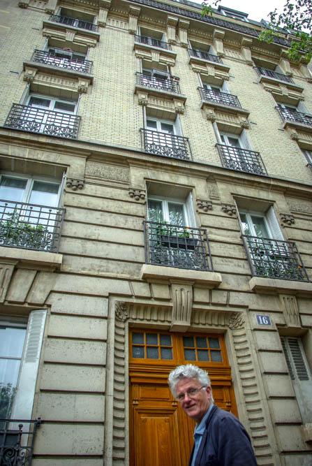 Gérard Mordillat encadré dans la porte de l'immeuble du 16 rue Belgrand @J.Barret