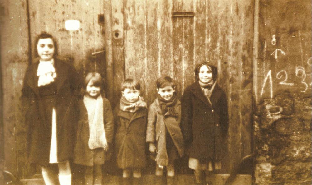 Groupe d'enfants devant une porte cochère passage des Muriers en novembre 1939. Le passage a disparu avec la ZAC des Amandiers @Parimagine - FPA